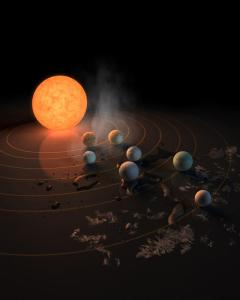 (022217)  This artist's concept appeared on the Feb. 23, 2017 cover of the journal Nature announcing that the TRAPPIST-1 star, an ultra-cool dwarf, has seven Earth-size planets orbiting it. Any of these planets could have liquid water on them. Planets that are farther from the star are more likely to have significant amounts of ice, especially on the side that faces away from the star. The system has been revealed through observations from NASA's Spitzer Space Telescope and the ground-based TRAPPIST (TRAnsiting Planets and PlanetesImals Small Telescope) telescope, as well as other ground-based observatories. The system was named for the TRAPPIST telescope. (Photo Courtesy of NASA/JPL - Caltech)
